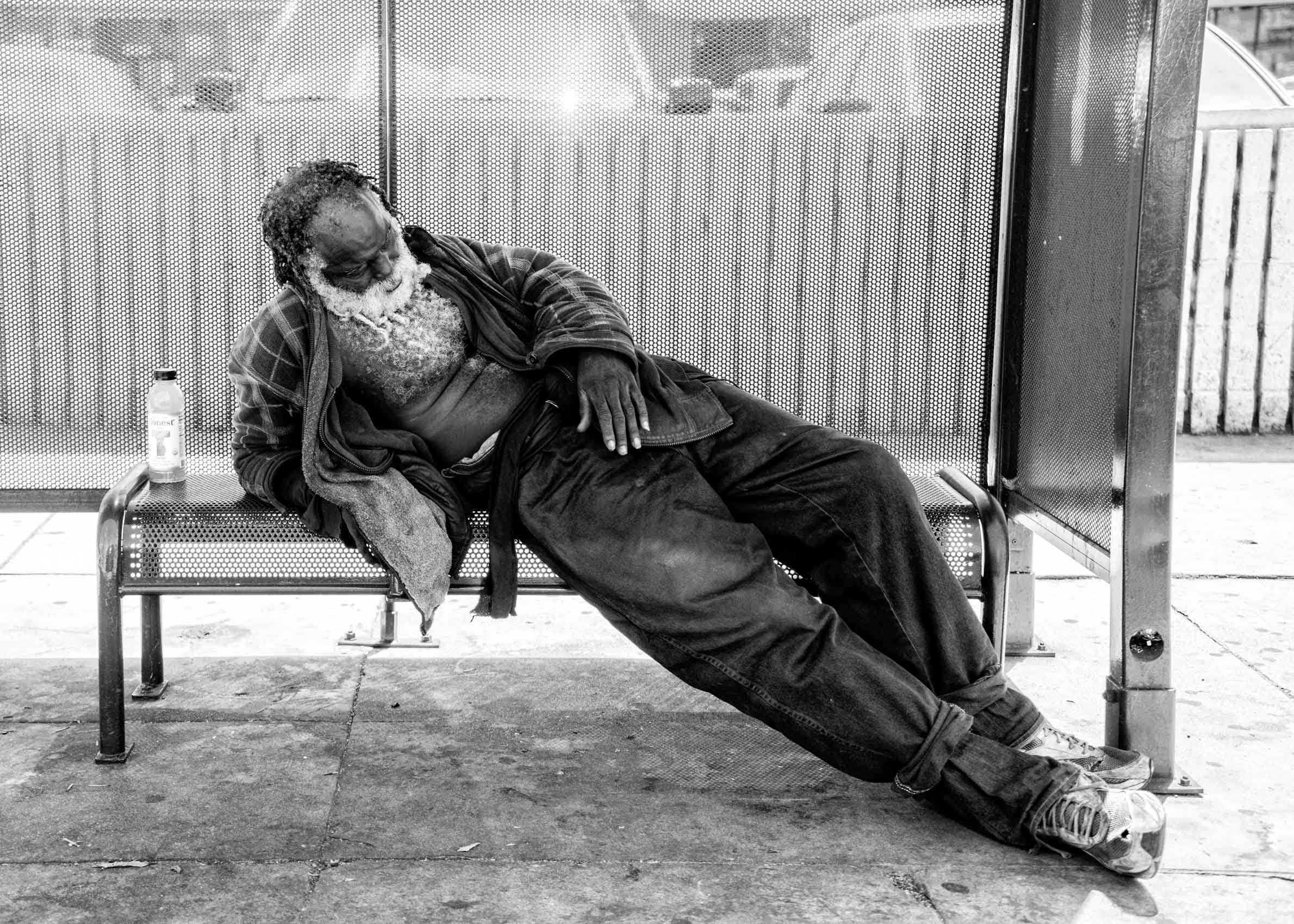 Los Angeles Street Photographer - Homeless man sitting at bus stop los angeles  by Ray Kachatorian
