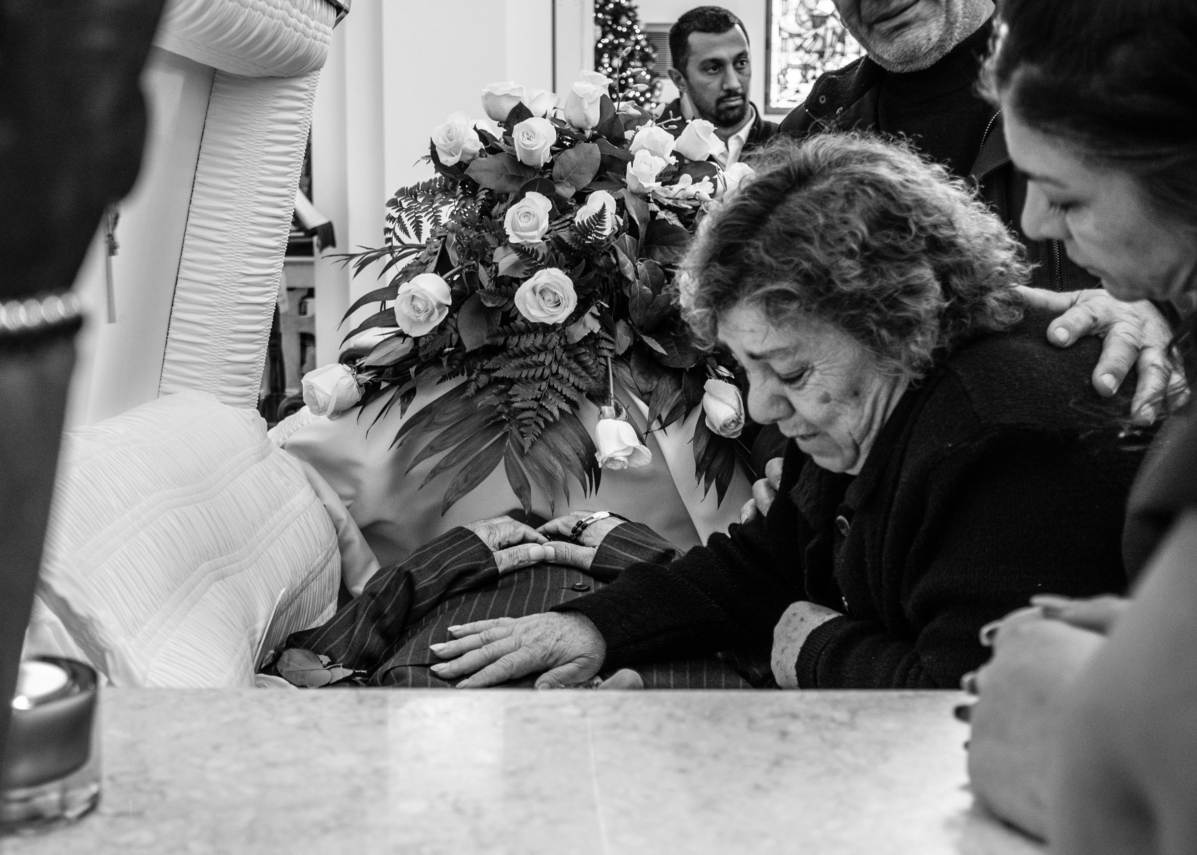 Los Angeles Street Photographer - Woman grieving over casket  by Ray Kachatorian